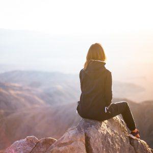 Peersona sentada en una roca mirando el horizonte